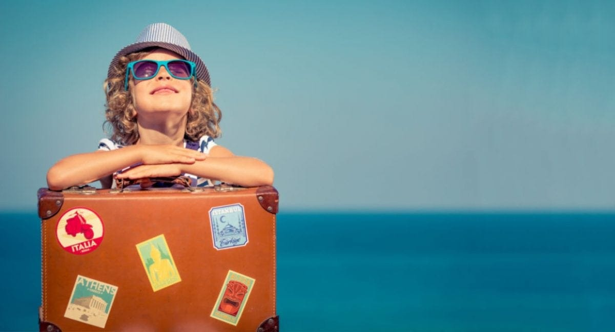 Boy in sunglasses and hat leaning on a suitcase in front of the ocean