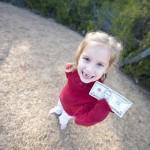 Little girl holding a dollar bill