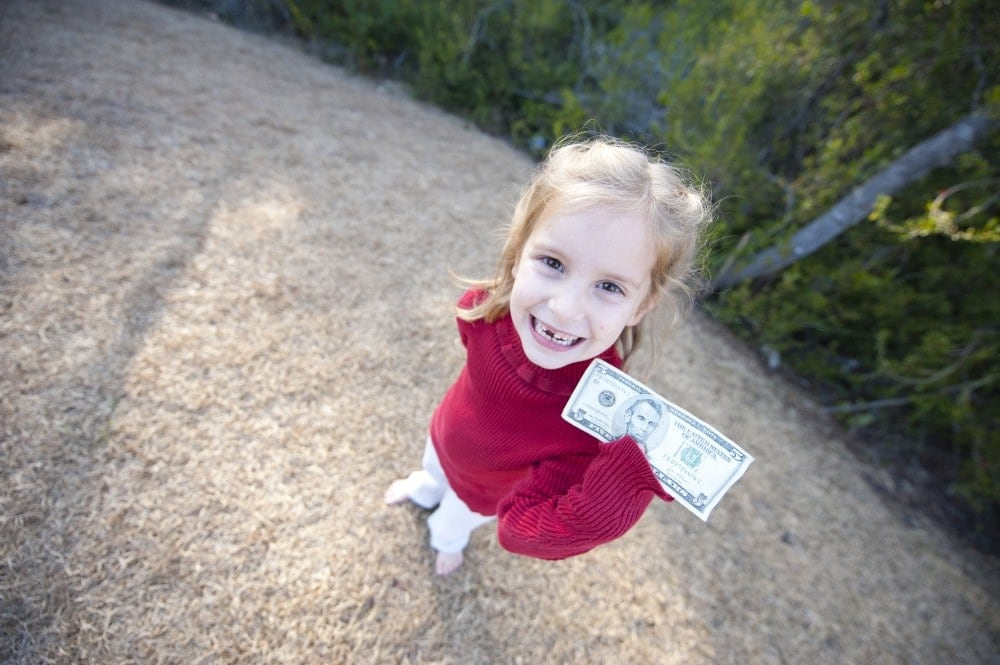 Little girl holding a dollar bill