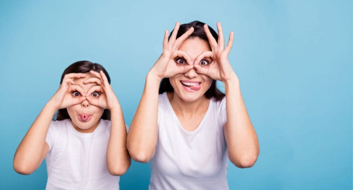 A mom and a daughter making glasses with their hands over their eyes