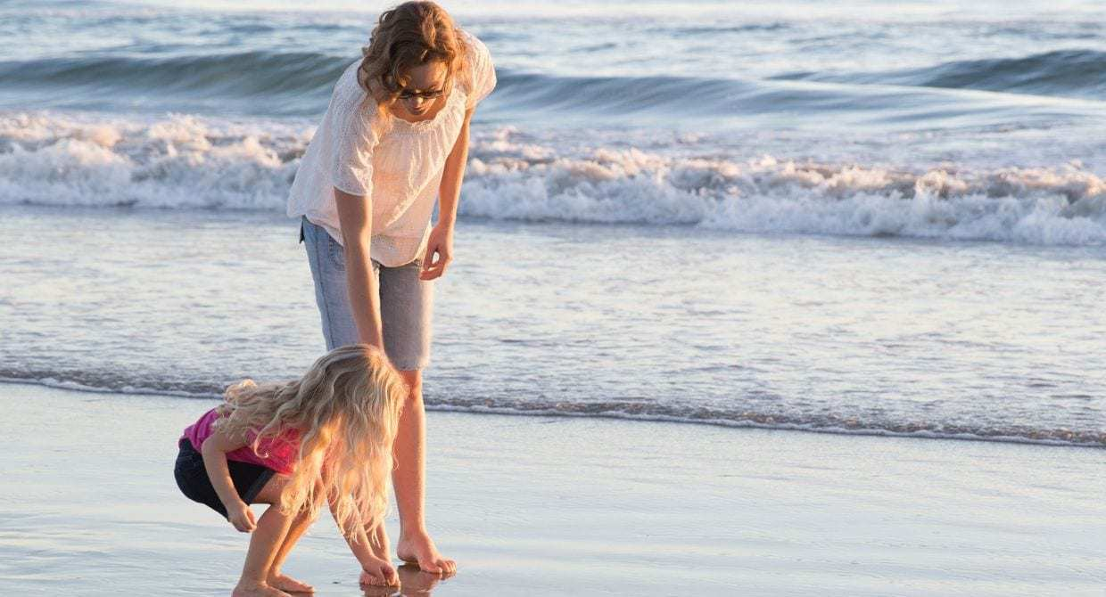 Mom and daughter at the beach picking up shells