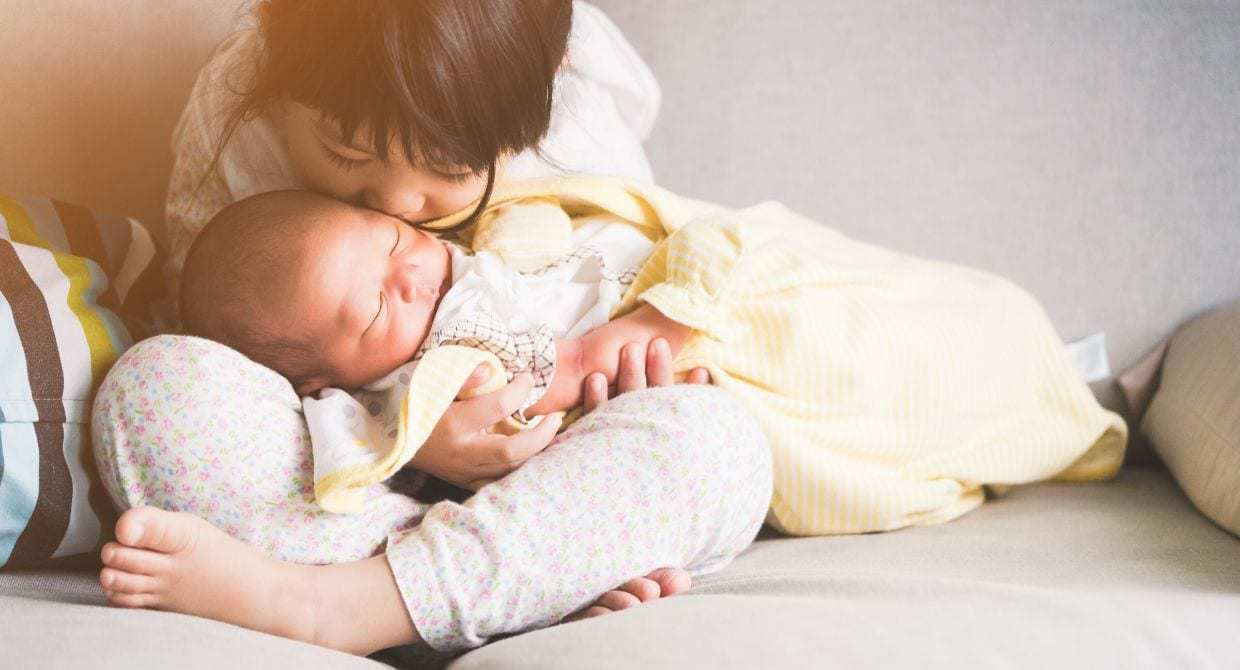 Little girl holding newborn baby and kissing forehead