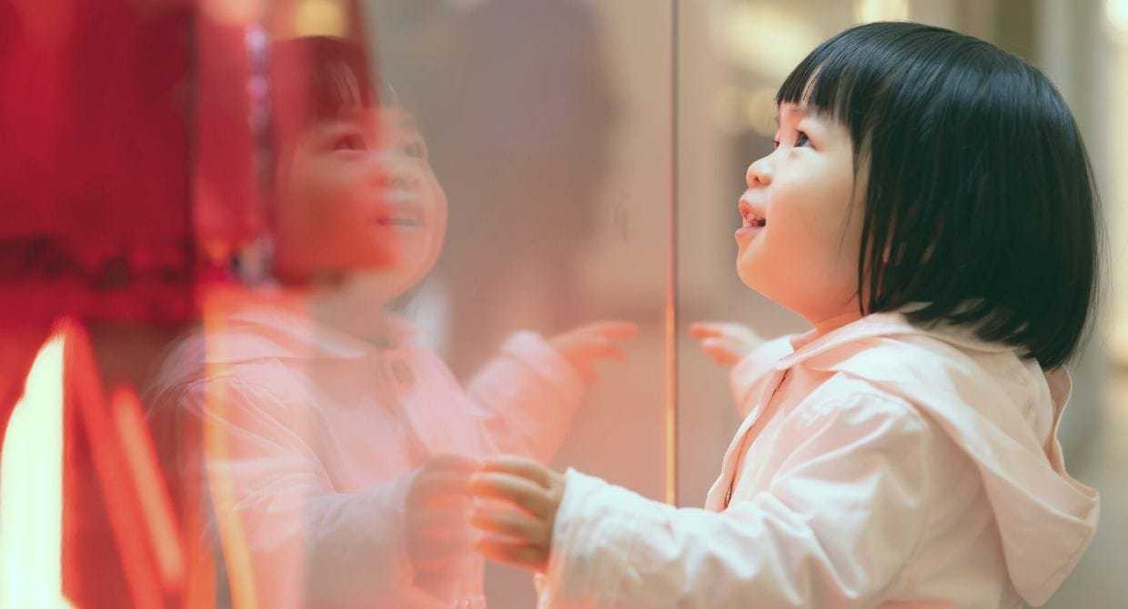 Little Asian girl staring into the window of a store front