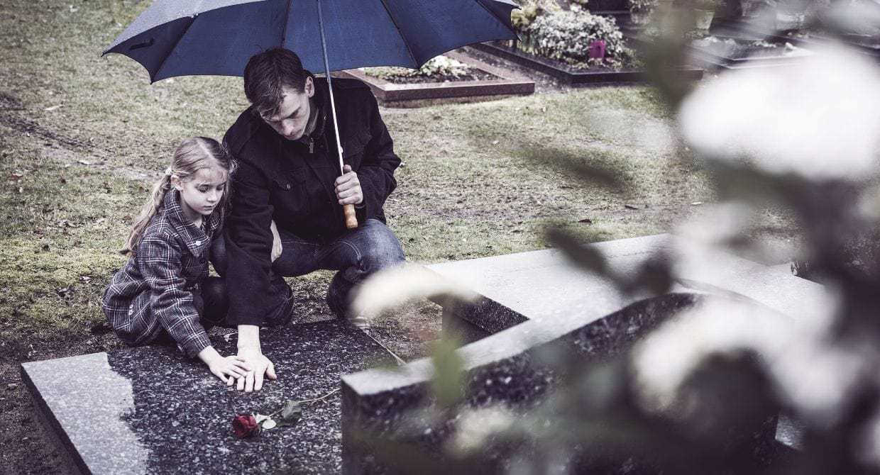 Girl and man putting flowers on a grave in the rain