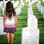 little girl standing in a cemetery of gravestones