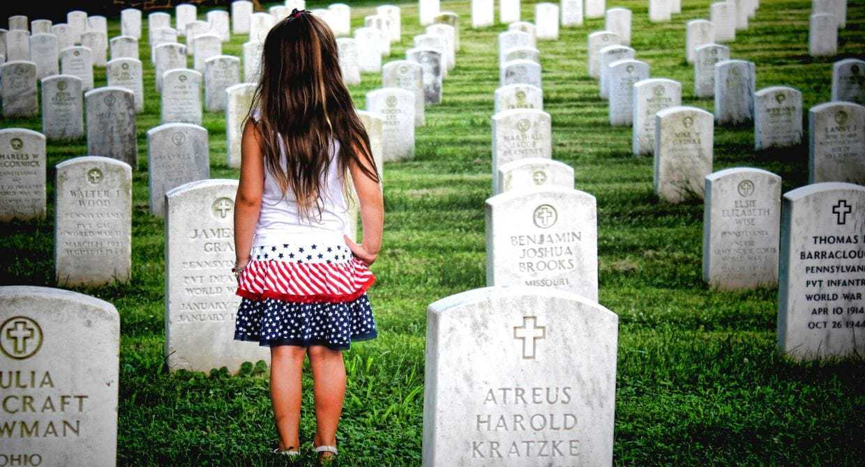 little girl standing in a cemetery of gravestones
