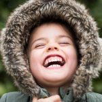 Child in winter coat laughing