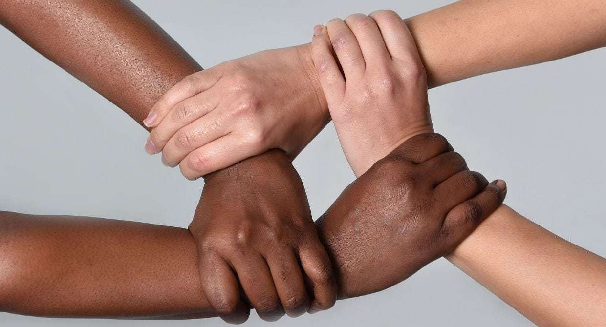 White hands and black hands hold each other
