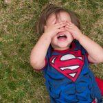 Little boy in super man shirt throwing a tantrum on the grass