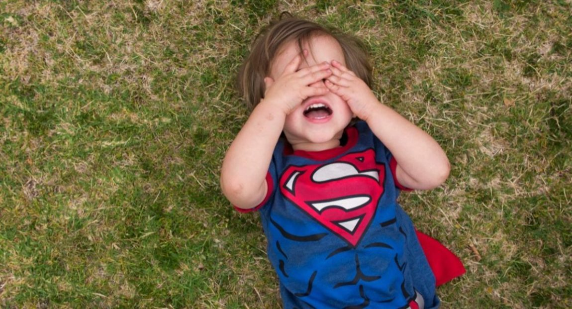 Little boy in super man shirt throwing a tantrum on the grass