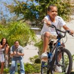 boy riding his bike with parents cheering