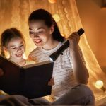 mom and daughter reading story with flashlight
