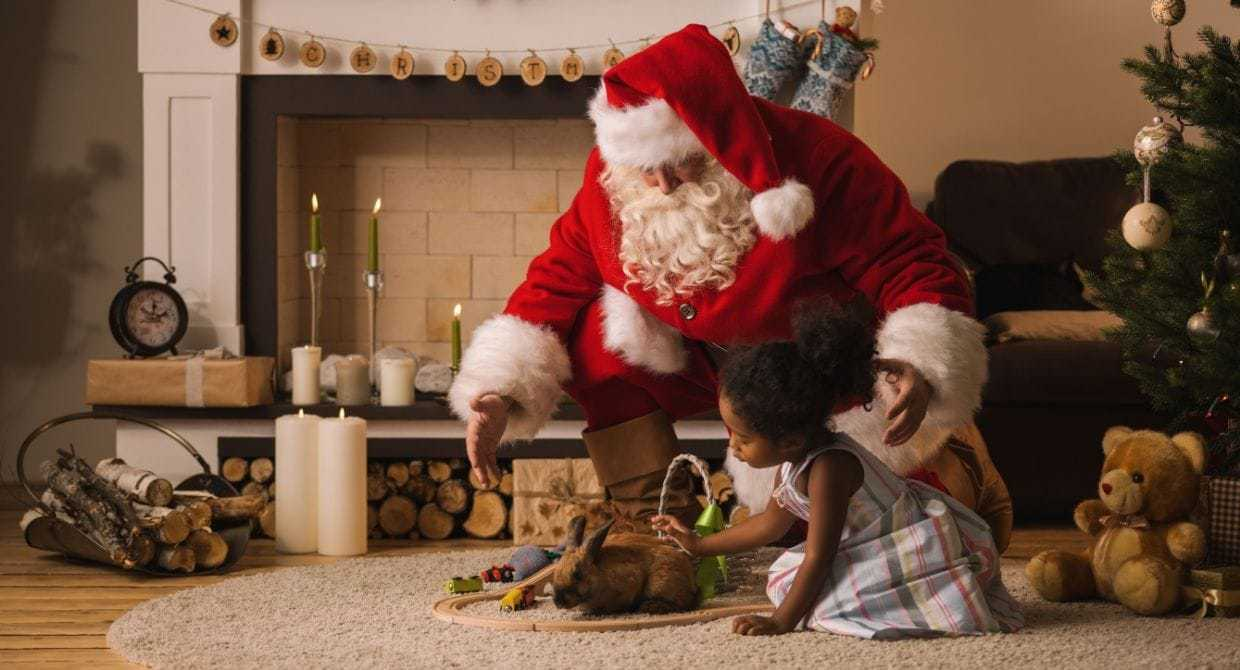 Santa playing with little girl around tree