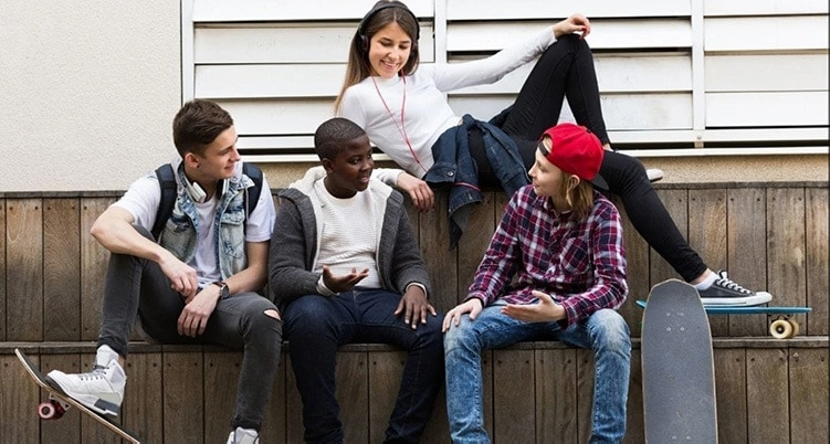 group of teens talking with skateboards and phones