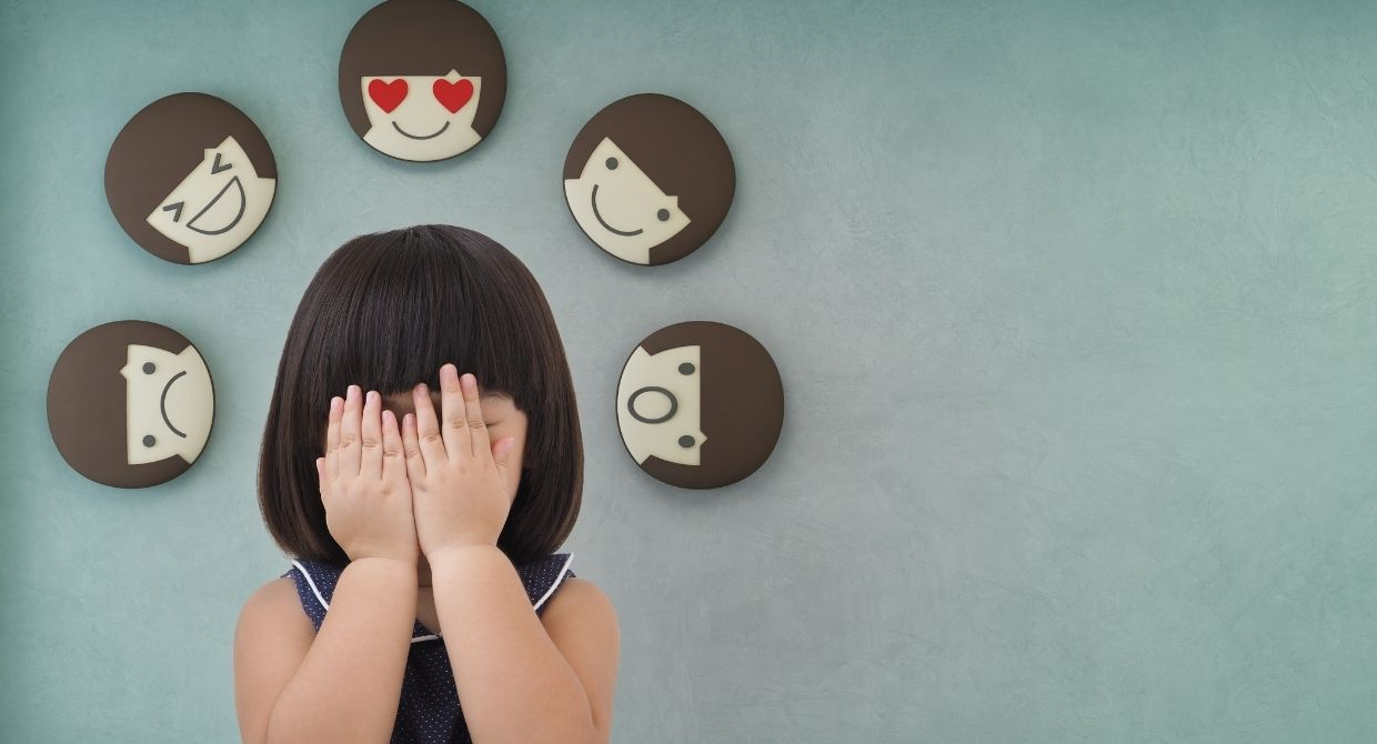 little girl covering her face with feelings emojis