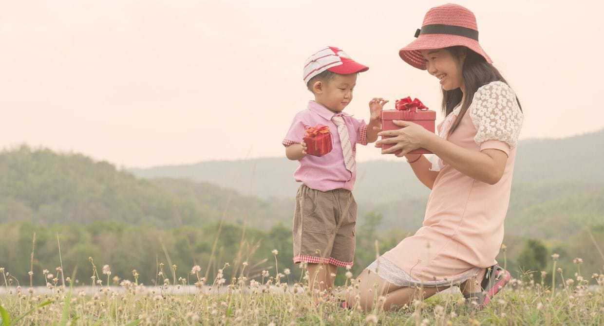 Asian mom and son exchanging gifts in a field