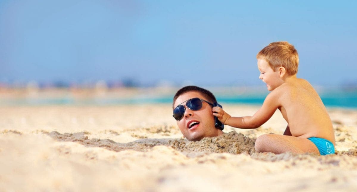 Dad buried in sand with child holding up a phone to his ear