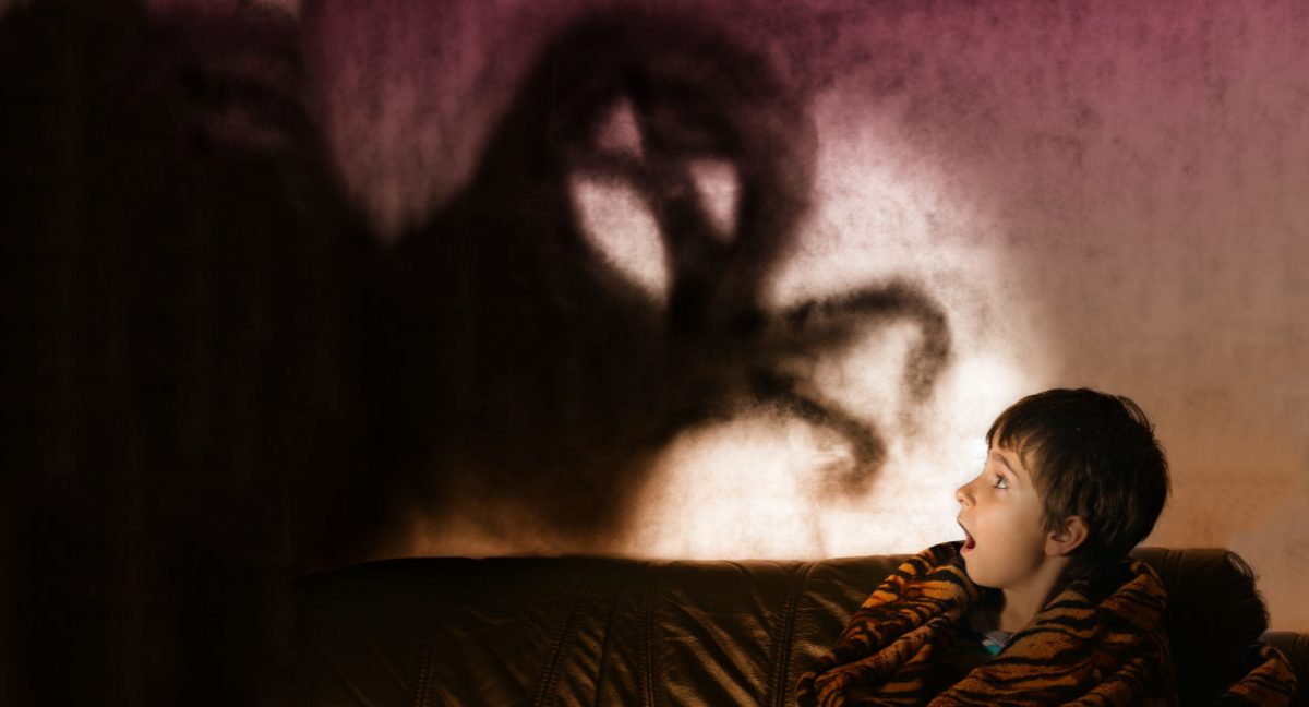 A shadow monster on the wall with a child scared in bed