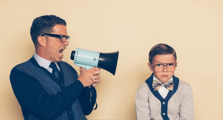 Man with megaphone yelling at boy