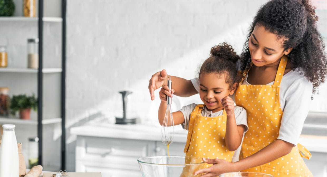Mom cooking with her young daughter