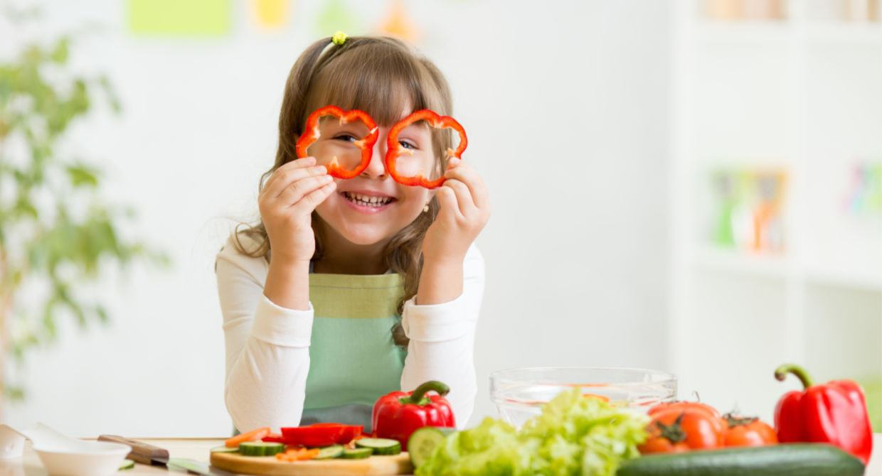 Young girl holding bell pepper slices over her eyes as glasses