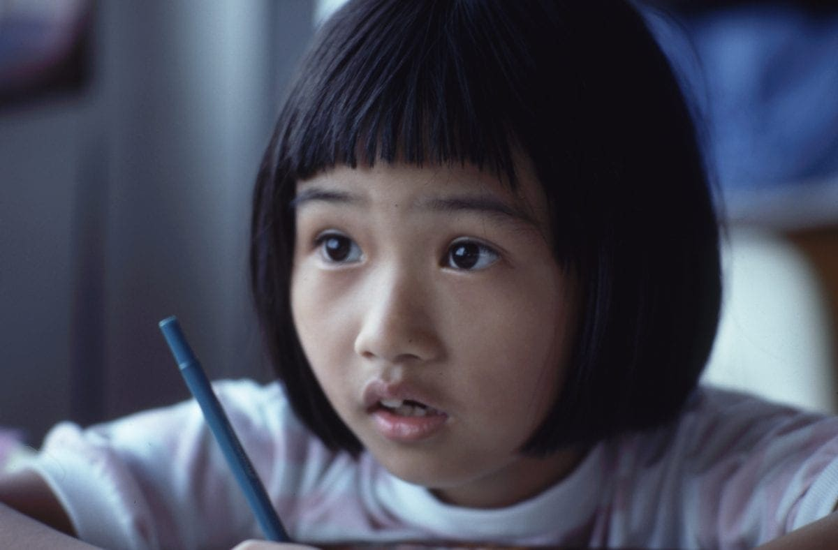 Young girl holding a pencil at her desk