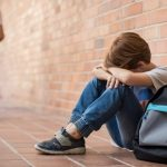 young boy bullied head on his knees