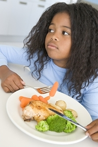 Young girl in kitchen eating chicken and vegetables