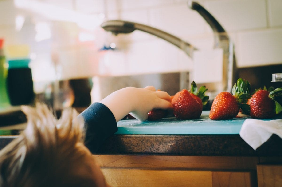 Little boy picking strawberries off a cutting board